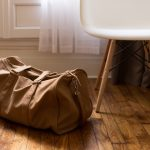 an image of wood flooring in a home with a bag and chair