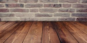 A picture of wood flooring against a brick wall
