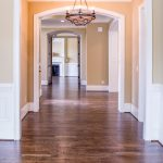 An image of a hallway with vinyl flooring and a chandelier