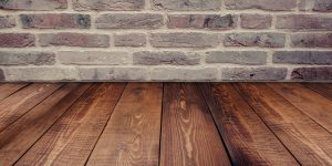 an image of a solid wood floor in front of a brick wall